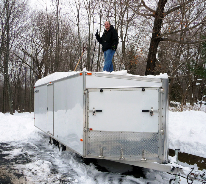 Man shoveling snow from trailer roof