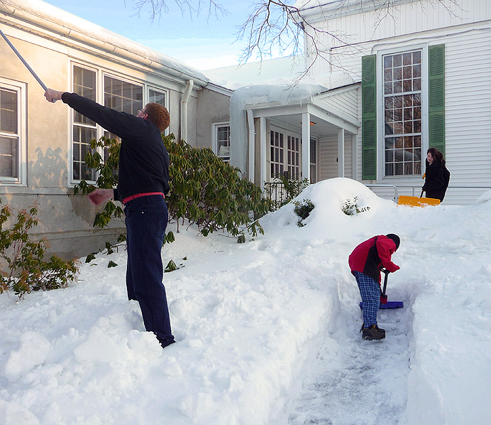 Family clearing snow